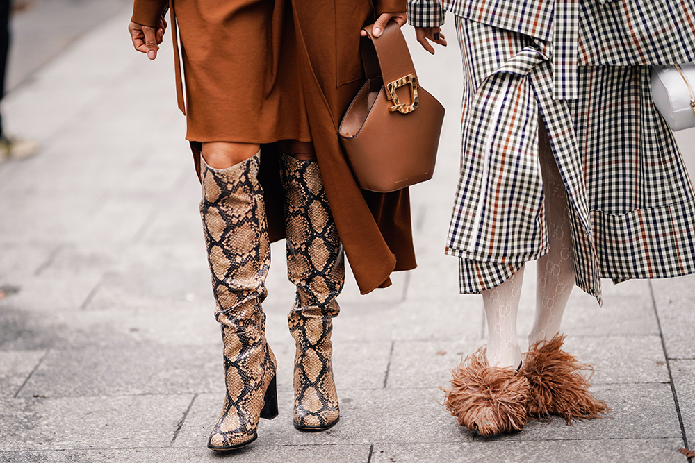 PARIS, FRANCE - MARCH 02: A guest (L) wears a brown dress, a brown Danse Lente bucket handbag, a brown python pattern boots ; a guest a brown and green suit, Gucci tights, brown ostrich feathers decorated shoes, outside Altuzarra, during Paris Fashion Week Womenswear Fall/Winter 2019/2020, on March 02, 2019 in Paris, France. (Photo by Edward Berthelot/Getty Images)