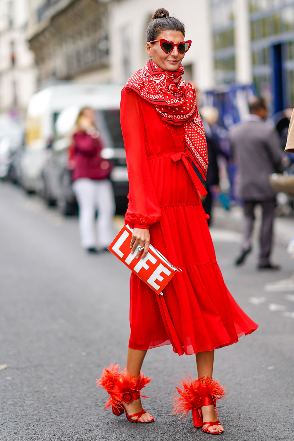 """PARIS, FRANCE - OCTOBER 02: Giovanna Battaglia wears a red dress, a red scarf, red heart sunglasses, a red """"LIFE"""" clutch, outside Giambattista Valli, during Paris Fashion Week Womenswear Spring/Summer 2018, on October 2, 2017 in Paris, France. (Photo by Edward Berthelot/Getty Images)"""