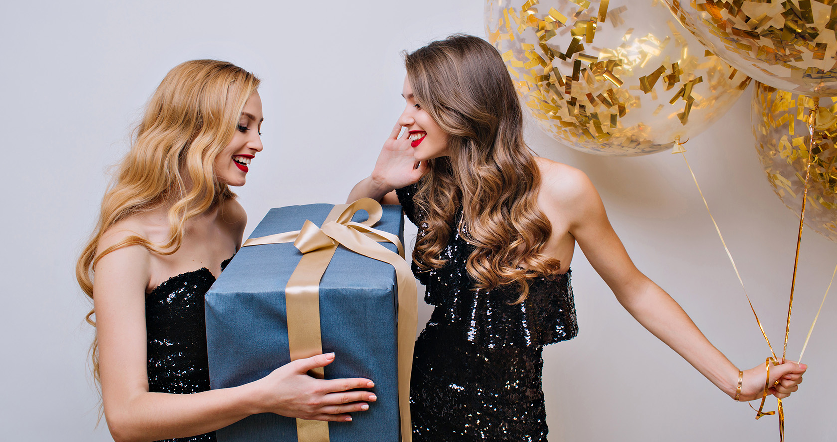 Amazing blonde girl received big present from female friend with light-brown hair. Indoor portrait of charming young woman holding gift for brunette sister which holding party balloons..